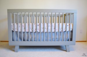 A grey and white nursery featuring the babyletto hudson crib in grey.