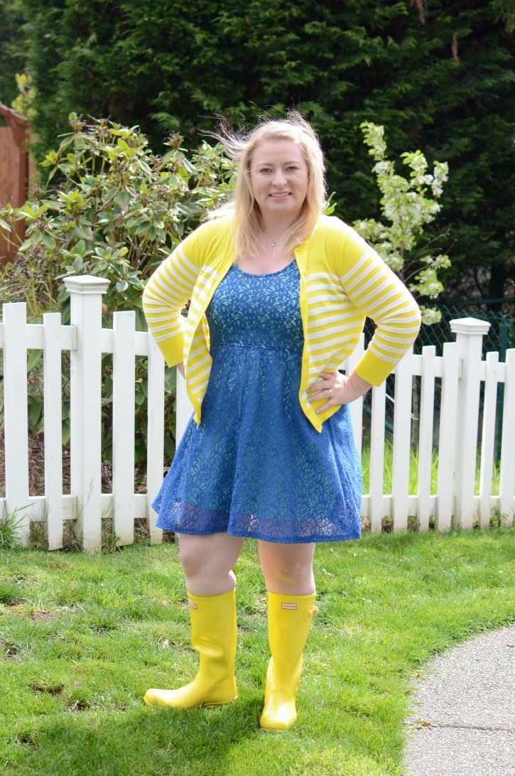 A fun outfit featuring yellow Hunter Rain Boots, a blue lace dress, and yellow cardigan