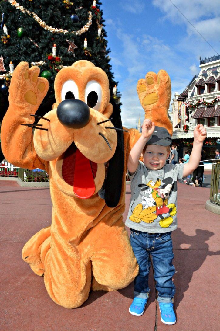 Toddler with Pluto at Walt Disney World doing Touchdown Pose