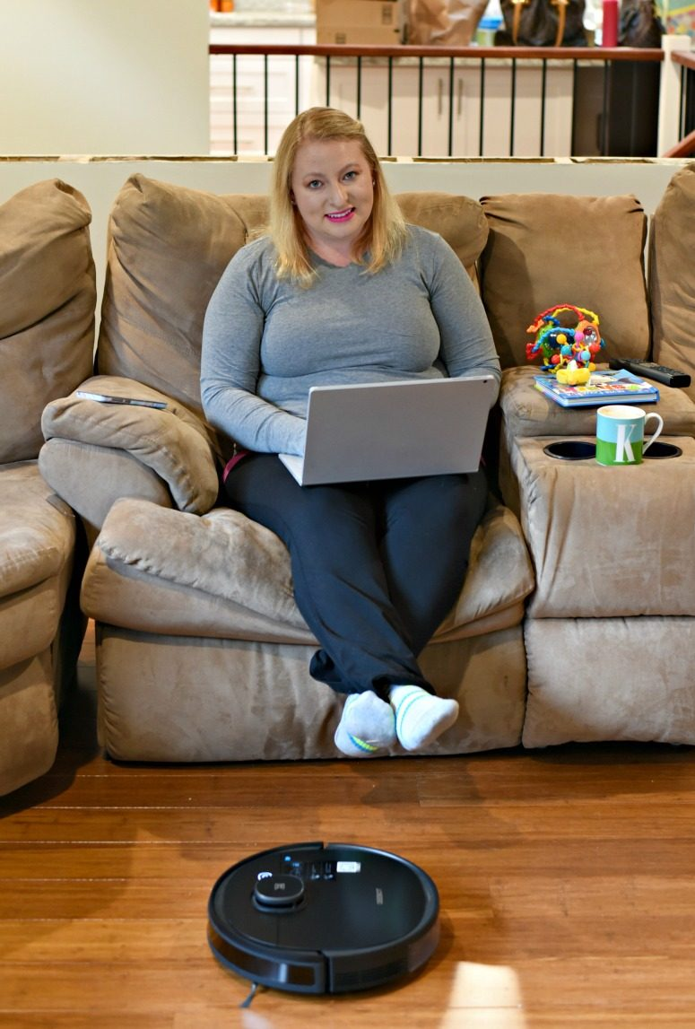 Woman on laptop with DEEBOT OZMO