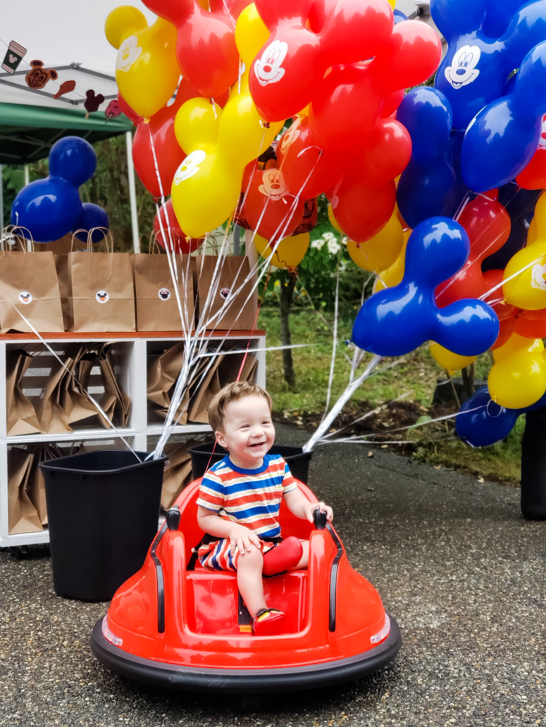 Baby on Ride-On Vehicle in front of Mickey Balloons