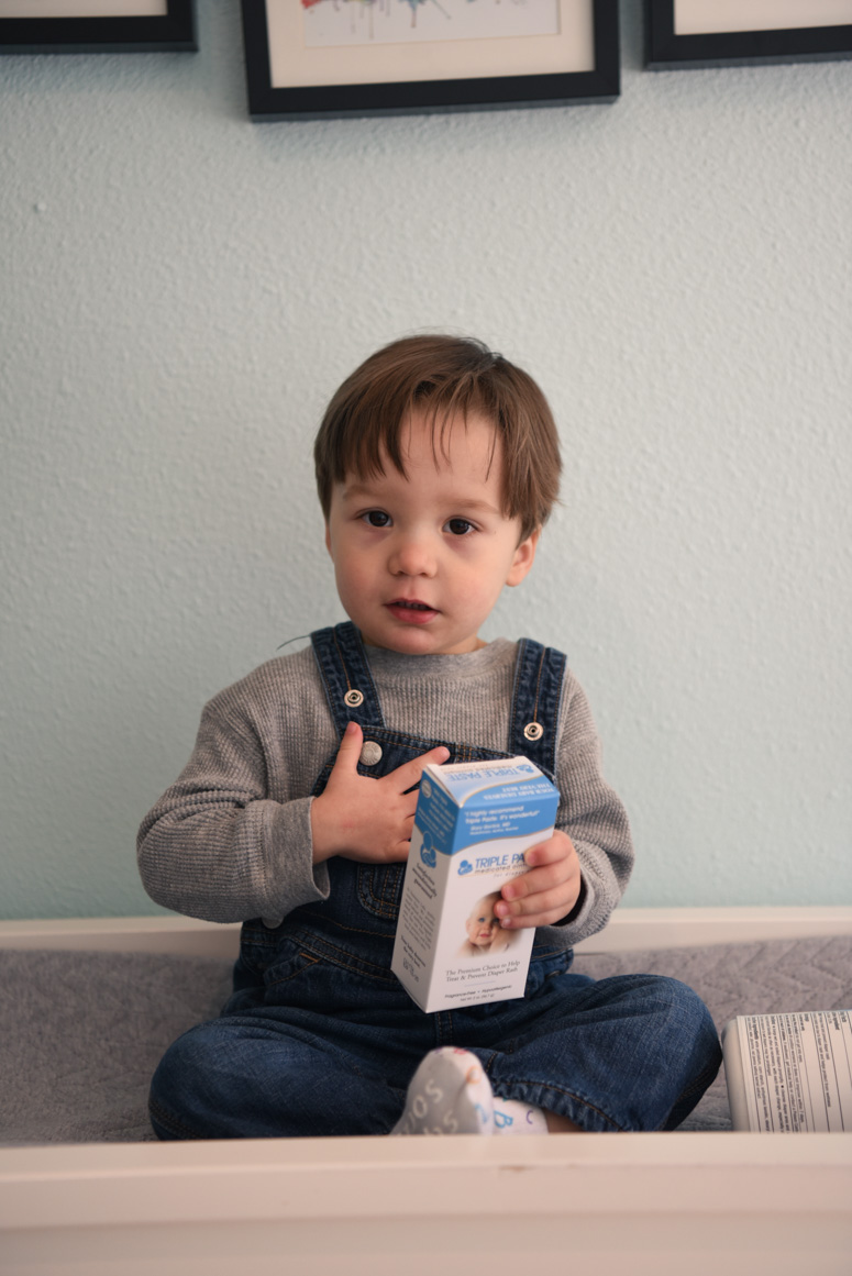 Toddler holding a box of triple paste diaper cream.